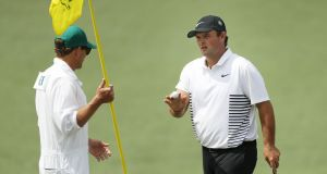 Patrick Reed waves on the second hole alongside caddie Kessler Karain during the second round of the 2018 US Masters at Augusta National Golf Club. Photo: Patrick Smith/Getty Images