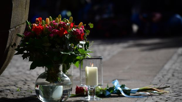 Flowers lay in front of the statue at the Kiepenkerl pub by the site of a deadly attack with a van in Münster, western Germany. Photograph: Alexander Koerner/Getty Images.