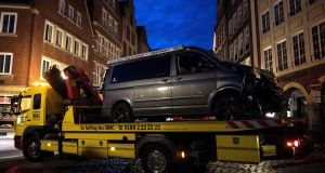 A tow truck removes a vehicle from the square where a man rammed his van into a crowd killing two and injuring several others in Münster, western Germany. Photograph: Marius Becker/AFP/Getty Images.