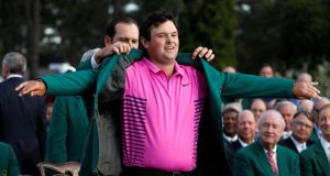 Sergio Garcia puts the green jacket on 2018 Masters winner Patrick Reed. Photograph: Reuters
