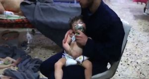 An image grab taken from a video released by the Syrian civil defence in Douma shows an unidentified volunteer holding an oxygen mask over a child's face at a hospital following a reported chemical attack on the rebel-held town on Sunday. Photograph: AFP/ HO / Syria Civil Defence