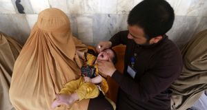 A member of a polio vaccination team administers vaccination to a child during a three-day countrywide vaccination campaign in Peshawar, Pakistan. Along with Afghanistan and Nigeria, Pakistan is one of the last three countries where polio is still endemic. Photograph: Arshad Arbab/EPA