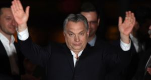 Hungarian Prime Minister Viktor Orbán celebrates on a podium on the bank of the Danube River after winning the parliamentary election with members of his Fidesz party on Sunday. Photograph: Attila Kisbenedek/AFP/Getty Images
