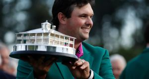 Patrick Reed holds the Masters tournament trophy, in his green jacket in Augusta. Photograph: Jonathan Ernst/Reuters
