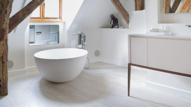 The hers bathroom, from West One bathrooms, is feminine in feel and includes a separate shower and freestanding round tub as well as a dressing table.