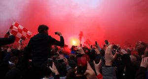 Fans let off flares as the the Manchester City team bus  arrived at Anfield  for their UEFA Champions League quarter-final, first leg match. Photograph: PA