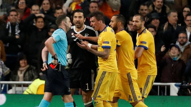 Buffon and teammates remonstrate with referee Michael Oliver after he awarded a penalty to Real Madrid. Photo: Paul Hanna/Reuters