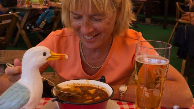 "Anne Gibney and her fluffy seagull Séamus lap up goulash in Hungary. She writes a travel blog, ""Gullible Travels, Diary of a Wandering Seagull"", with her husband Herwig who takes the photographs. www.gullibletravels.net"