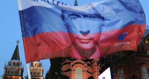 A Russian flag featuring Vladimir Putin  at the central Manezhnaya Square just outside the Kremlin in Moscow in 2012. Photograph: Alexander Nemenov/AFP/Getty Images