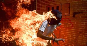 This image by Ronaldo Schemidt (Brazil) for AFP  was chosen as the World Press Photo of the Year ina ceremony in Amsterdam on Thursday night- Venezuela Crisis - Spot News, first prize stories - Jose Victor Salazar Balza (28) catches fire amid violent clashes with riot police during a protest against President Nicol?s Maduro, in Caracas, Venezuela.