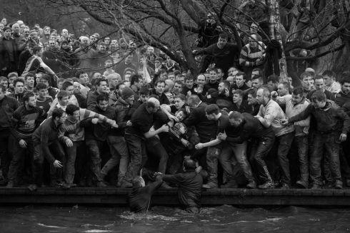 Royal Shrovetide Football - Oli Scarff, England (AFP) - Sports, first prize singles Members of opposing teams, the Upwards and Downwards, grapple for the ball during the historic, annual Royal Shrovetide Football Match in Ashbourne, Derbyshire, UK. The game is played between hundreds of participants in two eight-hour periods on Shrove Tuesday and Ash Wednesday (the day preceding and the day marking the start of Christian Lent).