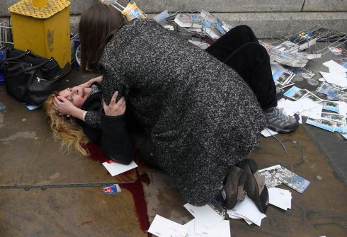 Toby Melville , UK (Reuters).  A passerby comforts an injured woman lying on the pavement after Khalid Masood drove his car into pedestrians killing four in addition to a police officer at Westminster Bridge in London, Britain, March 22, 2017.