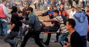 Palestinians evacuate an injured protestor during clashes  near the Israeli border fence in  Gaza. Photograph: AFP/Getty Images