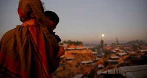 A Rohingya refugee carrying a child looks at the full moon at Balukhali refugee camp near Cox's Bazar, Bangladesh, late last year. File photograph: Susana Vera/Reuters