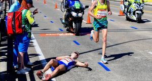 Scotland's Callum Hawkins lies on the ground as Australia's Michael Shelley runs past during the Men's Marathon Final at the Commonwealth Games on the Gold Coast in Australia. Photo: Tracy Nearmy/Reuters