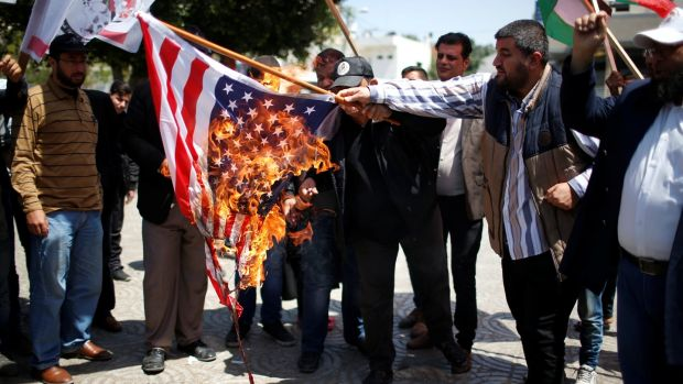 Palestinians burn a US flag during a protest against air strikes in Damascus, in Gaza city April 15, 2018. Photograph:Mohammed Salem/Reuters