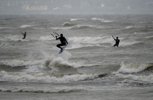 RIDING THE WAVES: Windsurfers ply their trade off Dollymount Strand in Dublin. Photograph: Cyril Byrne/The Irish Times