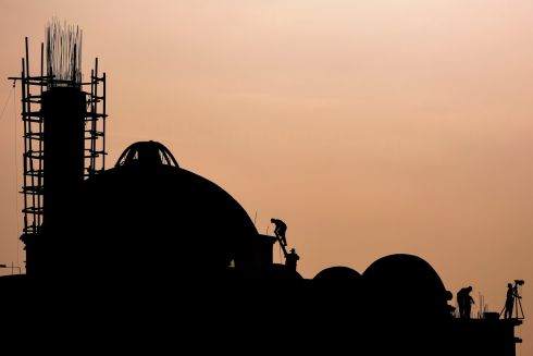 MOSQUE BUILDERS: Kosovans work on the construction of a new mosque as the sun sets on the outskirts of Pristina. Photograph: Armend Nimani/AFP/Getty Images