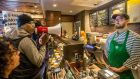 Local Black Lives Matter activist Asa Khalif, left, stands inside a Starbucks, Sunday April 15th, 2018, demanding the firing of the manager who called police resulting the arrest of two black men on Thursday. Photograph: Mark Bryant/AP