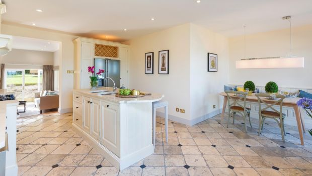 The large fitted kitchen from Design House in Dalkey has cream units, a stone tiled floor and polished stone countertops and island unit