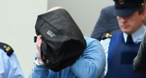 The Supreme Court has refused to hear an appeal by Michael Murray (in blue jumper, hiding behind black bag) against an increase in his jail sentence from 15 to 19 years. File photograph: Courts Collins