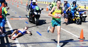 Australia's Michael Shelley  passes a prone Callum Hawkins of Scotland as he collapses after being in the lead of the Men's Marathon Final  at the XXI Commonwealth Games on the Gold Coast, Australia. Photograph: Tracey Nearmy/EPA