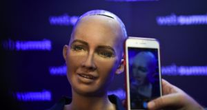"A woman takes pictures of Humanoid ""Sophia The Robot"" of Hanson Robotics  at the 2017 Web Summit in Lisbon. Photograph: Patricia de Melo Moreira/AFP/Getty Images"