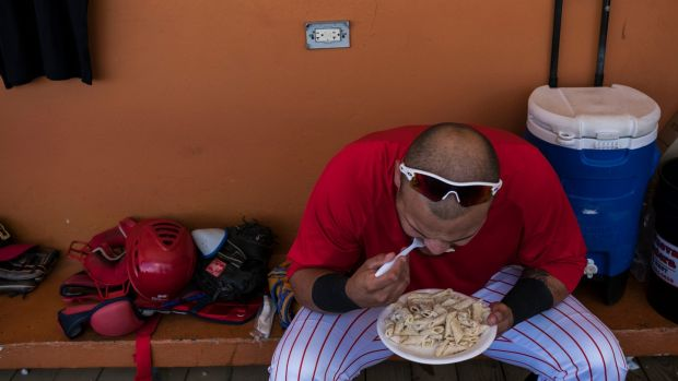 Cayey Toritos catcher Raulier Martinez eats in the dugout between games. Photograph: Dennis M Rivera Pichardo/The New York Times