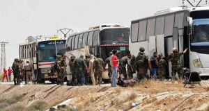 Russian soldiers and Syrian government forces oversee the evacuation of rebel fighters from the Army of Islam and their families from the town of Dumayr, northeast of Damascus, on Thursday. Photograph Sana (official Syrian news agency)/via AP)