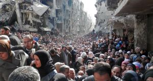 A file photograph of people waiting in line for food at the Yarmouk refugee camp in Damascus, taken on January 31st, 2014. Photograph: United Nation Relief and Works Agency via Getty Images