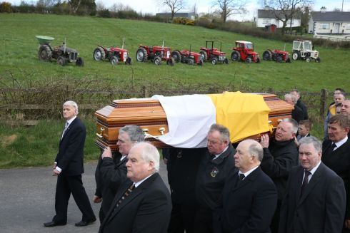 GOOD VINTAGE: The funeral cortege of Big Tom McBride makes it way to Saint Patrick's Church in Oram, Co Monaghan, for his funeral on Friday, passing a line of vintage tractors - some of which belonged to the singer. Photograph: Brian Lawless/PA Wire
