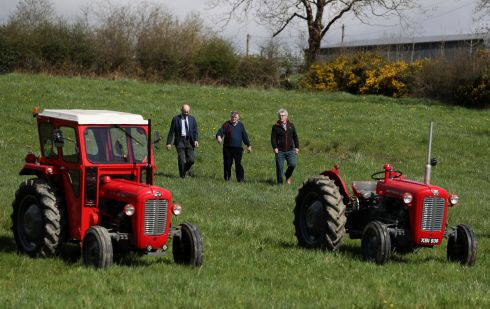 KEEP IT COUNTRY: Members of Castleblayney Vintage Club park well-seasoned tractors in a field opposite Saint Patrick's Church ahead of the funeral. Big Tom was a collector of them himself. Photograph: Brian Lawless/PA Wire