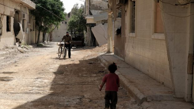 People walk in the recently recaptured Douma, on the outskirts of Damascus, Syria. Photograph: Youssef Badawi/EPA