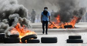 A masked protester walks between burning barricades in Managua, Nicaragua. Photograph: AP Photo/Alfredo Zuniga