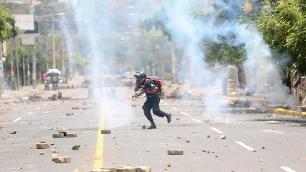 A police officer runs away from homemade mortars launched by demonstrators during clashes in Managua, Nicaragua. Photograph: AP Photo/Alfredo Zuniga