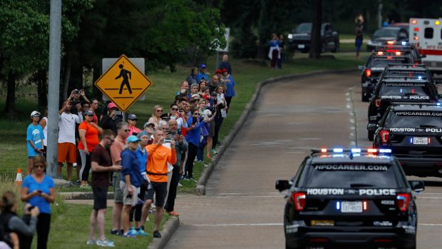 Onlookers wave as the motorcade carrying former first lady Barbara Bush's body is seen along Memorial Drive in Houston, Texas, the US. Photograph: Aaron M Sprecher/EPA