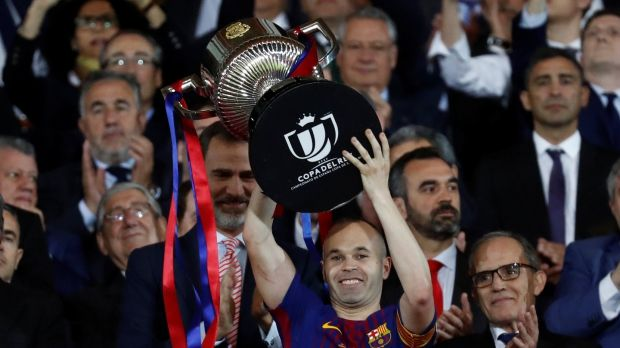 Barcelona captain Andres Iniesta lifts the trophy King Felipe VI applauds. Photograph: Juan Medina/Reuters
