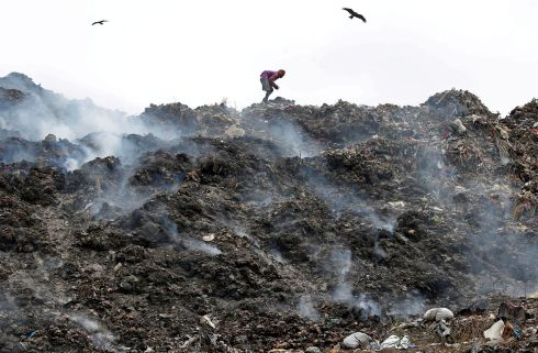 EARTH DAY: A man collects recyclable materials as smoke billows from a burning dump on the occasion of Earth Day, in Kolkata, India. Photograph: Rupak De Chowdhuri/Reuters