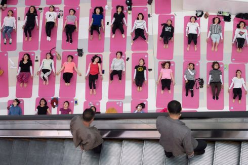 CENTRE OF GRAVITY: Men look at women attending a yoga session inside a shopping centre in Taiyuan, Shanxi province, China. Photograph: Stringer/Reuters