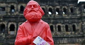 "A Karl Marx figure with a ""zero euro"" bank note which has been produced in his home city of Trier, Germany, as part of bicentenary celebrations. Photograph: Harald Tittel/AFP/Getty Images"
