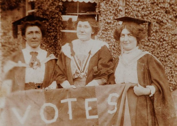 "Hanna Sheehy-Skeffington, Kathleen Shannon and Kate Sheedy, in their graduation robes and mortar-boards, carrying a banner saying ""Votes"" (for women)"