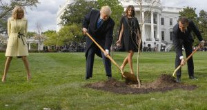 US president Donald Trump and French president Emmanuel Macron plant a tree watched by Mr Trump's wife Melania and Mr Macron's wife Brigitte on the grounds of the White House in Washington on Monday. Photograph: Jim Watson/AFP/Getty Images