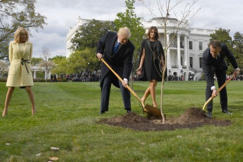 US President Donald Trump and French President Emmanuel Macron plant a tree watched by Trump's wife Melania and Macron's wife Brigitte on the grounds of the White House April 23, 2018 in Washington,DC. / AFP PHOTO / JIM WATSONJIM WATSON/AFP/Getty Images