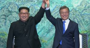Kim Jong-un and Moon Jae-in raise their hands after signing on a joint statement at the border village of Panmunjom in South Korea. Photograph: Korea Broadcasting System via AP