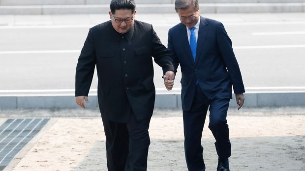 Kim Jong-un, North Korea's leader and Moon Jae-in, South Korea's president, hold hands as they cross the Military Demarcation Line to the southern side of the border at the village of Panmunjom. Photograph: Inter-Korean Summit Press Corps/Pool via Bloomberg