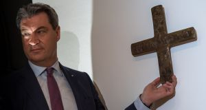 Bavarian state premier Markus Soeder hangs a cross in the entrance area of the state chancellery last Tuesday. Photograph:  Peter Kneffel/AFP/Getty Images