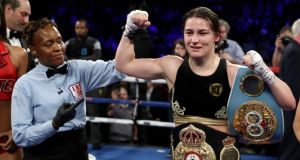 Katie Taylor with her WBA and IBF belts after her unanimous points win over Victoria Bustos. Photograph: Elsa/Getty