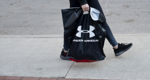 A pedestrian carries an Under Armour, shopping bag in Detroit, Michigan. Under Armour topped Wall Street forecasts for first-quarter revenue on Tuesday. Photographer: Rachel Woolf/Bloomberg