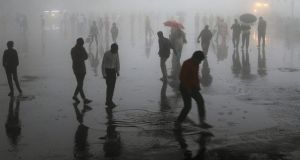 People walking under heavy rainfall and dust in the northern  town of Shimla in Himachal Pradesh state, India on Wednesday. Photograph:  AFP/Getty Images.