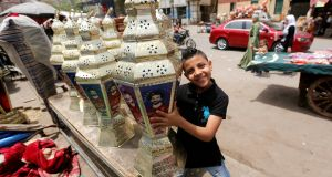 "An Egyptian boy carries the traditional decorative lanterns known as ""Fanous"" bearing the image of Liverpool's Egyptian player Mohamed Salah at a market in Cairo  before the beginning of the holy fasting month of Ramadan. Photograph: Amr Abdallah Dalsh/Reuters"